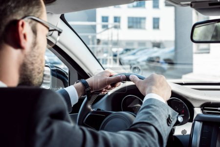 selective focus of businessman driving car alone
