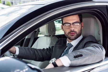 portrait of businessman in eyeglasses driving car