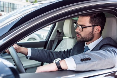 Photo for Side view of businessman in eyeglasses driving car - Royalty Free Image