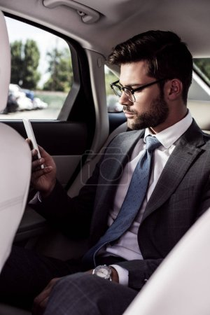 side view of confident businessman using smartphone on backseat in car