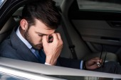 side view of tired businessman with eyeglasses sitting on backseat of car