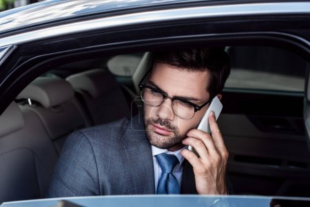 portrait of businessman talking on smartphone on backseat in car