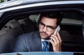 portrait of businessman talking on smartphone on backseat in car