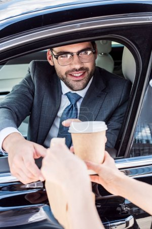 cropped shot of smiling businessman taking coffee to go and take away food from waiter while sitting in car