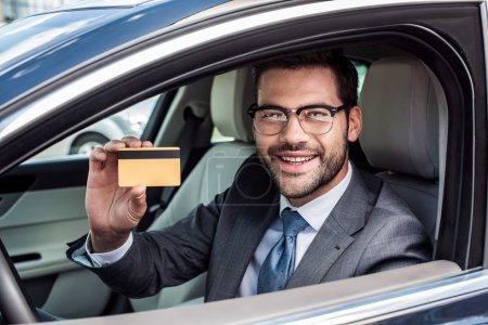 portrait of smiling businessman showing credit card in hand while sitting in car
