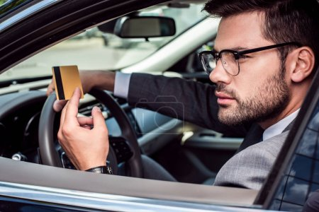 side view of businessman with credit card in hand sitting at steering wheel in car