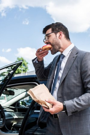 side view of businessman eating take away doughnut while standing at car on street
