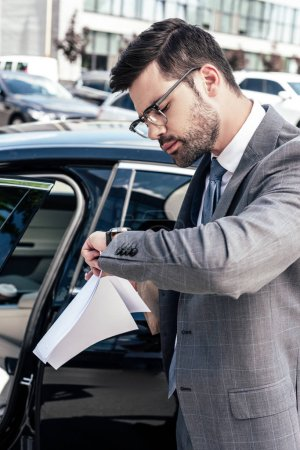 businessman with take away food and papers in hands checking time while standing at car on street