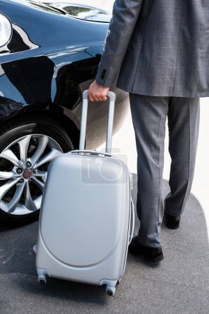 cropped image of businessman carrying wheeled bag near car at street