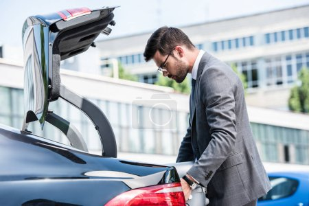 side view of businessman in eyeglasses putting wheeled bag in car trunk at street