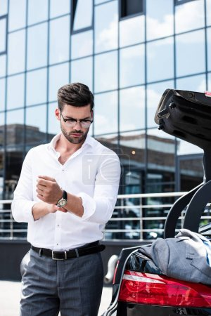 handsome businessman in eyeglasses rolling sleeves of white shirt near car trunk at street