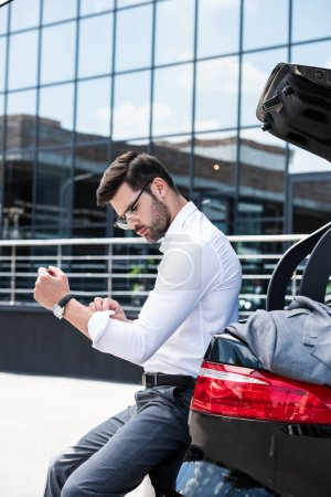 side view of businessman in eyeglasses rolling sleeves of white shirt while sitting on car trunk at street