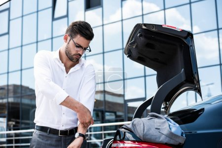 young businessman in eyeglasses rolling sleeves of white shirt near car trunk at street