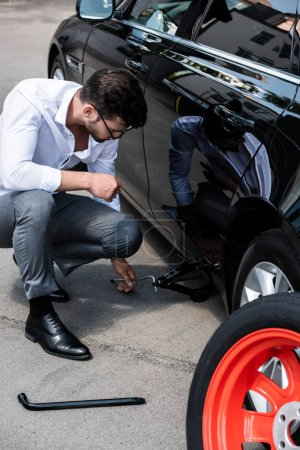 young businessman sitting near broken car and using jack screw at street