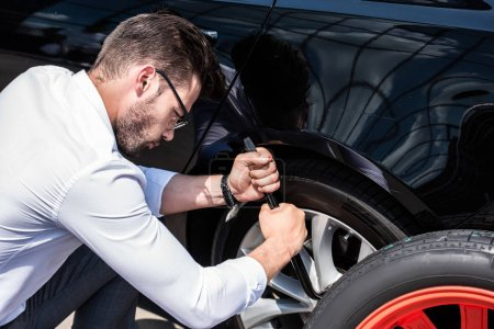 Photo for Side view of focused young businessman in eyeglasses using wheel spanner for wheel replacement at street - Royalty Free Image