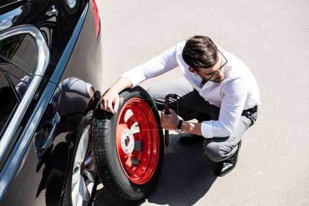 high angle view of young businessman replacing wheel of car at street