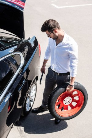 high angle view of young businessman in eyeglasses holding wheel spanner and tire near car at street