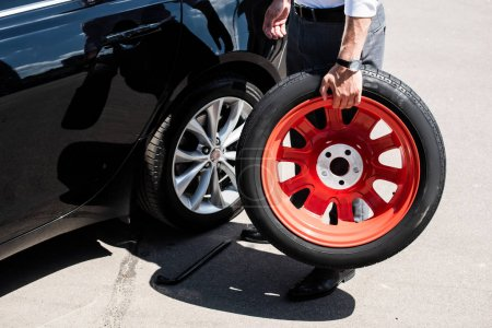 cropped image of businessman holding tire for wheel replacement at street