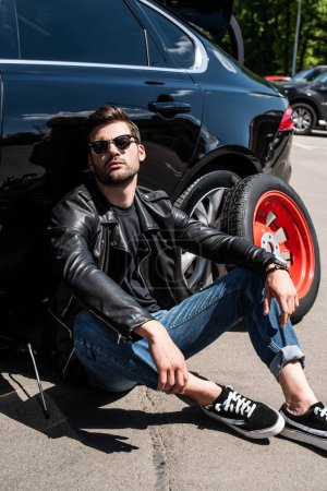 tired stylish man in sunglasses sitting near broken car at street
