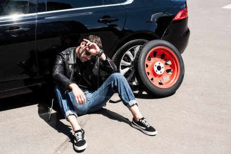 stylish tired man in sunglasses wiping forehead near tools, tire and broken car at street