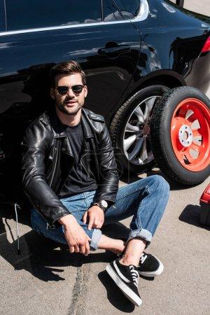 smiling stylish man in sunglasses sitting near broken car at street