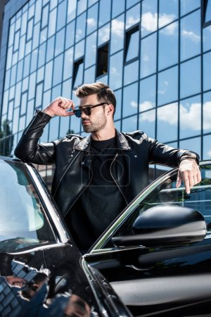stylish man in leather jacket and sunglasses looking away near car at street