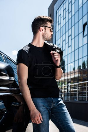 side view of stylish man in sunglasses holding leather jacket on shoulder near car at street