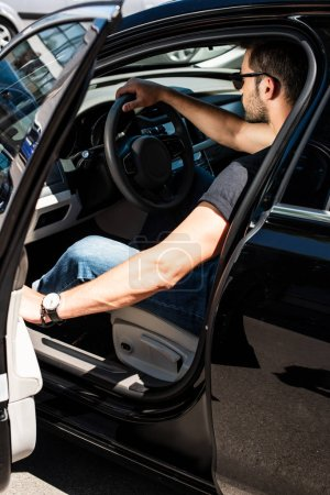 side view of stylish man in sunglasses closing door of his car at street