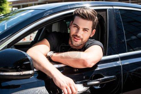 Photo pour Portrait de souriant beau jeune homme assis dans sa voiture - image libre de droit