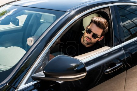 Photo pour Confiant jeune homme élégant dans des lunettes de soleil au volant de sa voiture - image libre de droit