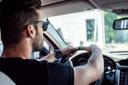 rear view of confident young stylish man in sunglasses driving his car