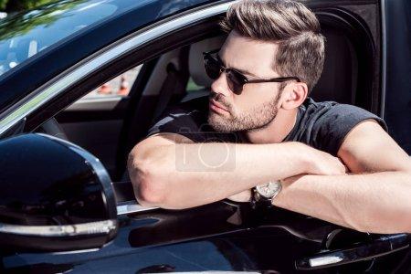 Photo pour Portrait de l'homme élégant sérieux dans lunettes de soleil à la recherche de suite assis dans sa voiture - image libre de droit