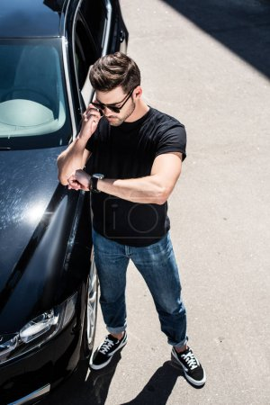 high angle view of stylish young man in sunglasses checking wristwatch near his car at street