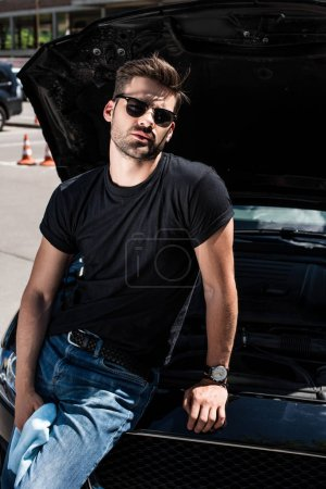 handsome young man in sunglasses with rag near car with opened bonnet at street