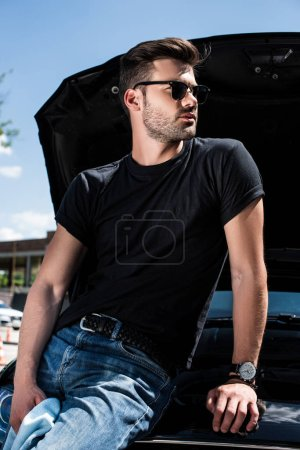 side view of young man in sunglasses with rag near car with opened bonnet at street