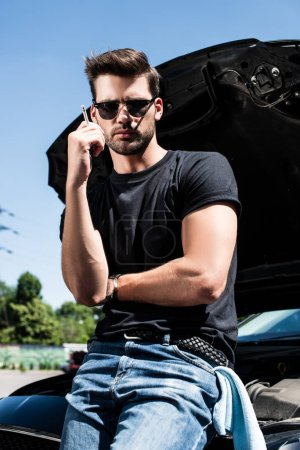 young stylish man in sunglasses smoking cigarette near broken car with opened bonnet