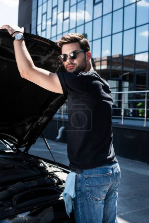stylish man in sunglasses closing bonnet of car at street
