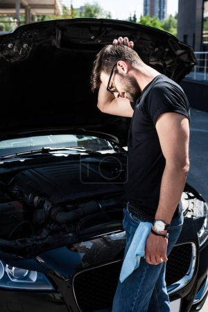 side view of confused man scratching head near broken car engine at street