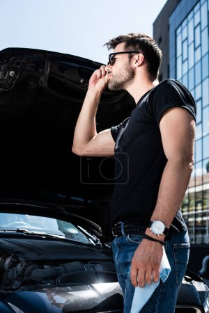 low angle view of stylish man in sunglasses standing near broken car with opened bonnet
