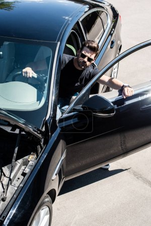 high angle view of stylish man in sunglasses going out from car with opened bonnet