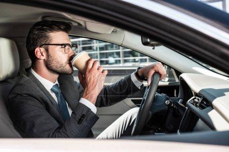 Photo pour Vue latérale de l'homme d'affaires en lunettes de boire du café et de l'équitation de voiture - image libre de droit