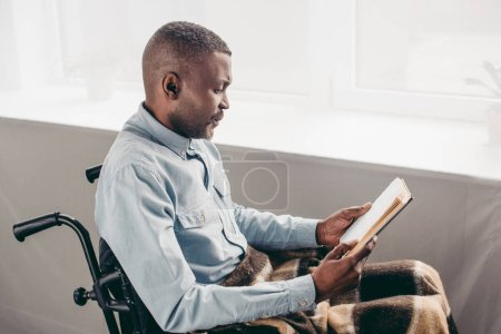 senior african american man in wheelchair reading book