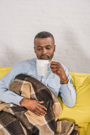 senior african american man drinking tea while sitting on sofa with plaid