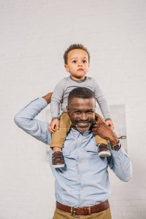 happy african american grandfather carrying little grandchild on neck and smiling at camera