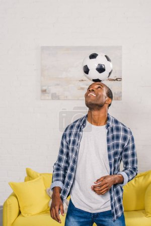 smiling young african american man balancing soccer ball on head at home