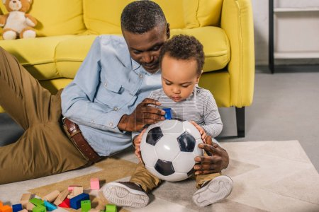 happy grandfather and little grandson playing with soccer ball and colorful blocks at home