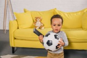 adorable african american toddler holding soccer ball and remote controller at home
