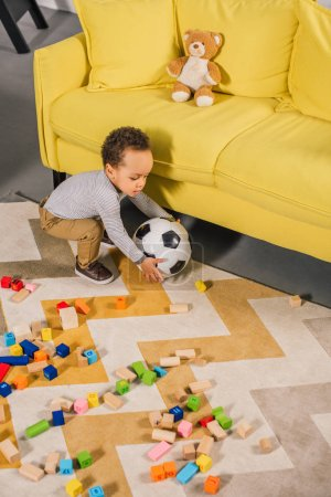 high angle view of cute little child playing with soccer ball and colorful blocks at home