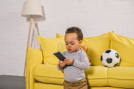 adorable little african american child holding remote controller at home