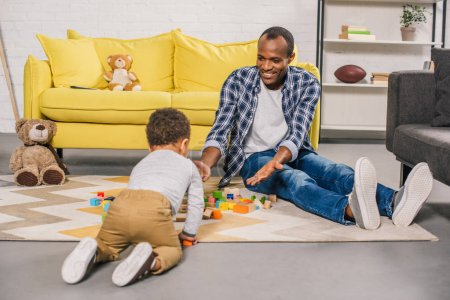 happy african american father and little son playing with colorful blocks at home